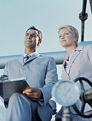 Business man and woman looking away in oil refinery,low angle view