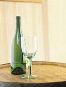 Wine bottle and glass on barrel,close_up
