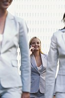 Three businesswomen walking, one using mobile phone