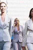 Three businesswomen walking on street, one using mobile phone