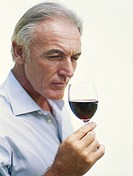 Mature man sniffing glass of red wine, close_up