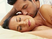 Young couple on bed, man kissing woman, close_up