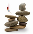 Stack of balanced rocks and falling feather, white background