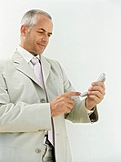 Young business man text messaging by white wall
