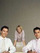Portrait of three young office workers,woman in centre leaning on desk,men sitting,differential focus