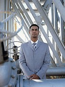 Business man at oil refinery in front of metal construction