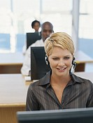 Businesspeople using computer, wearing headset