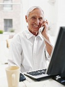 Senior man sitting computer using landline phone, smiling