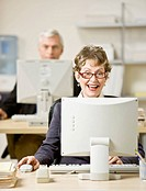 Man and woman working at computers in office focus on foreground