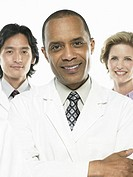 Three doctors on white background, smiling, portrait