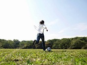 Woman running with football in park, ground view, rear view
