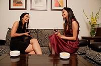 two women talking, drinks in hand horizontal
