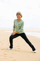 full body portrait of mature woman exercising on beach