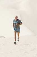 mature man running on sandy beach