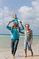 grandparents walking along beach with grandfather carrying young girl piggback