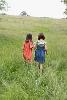 Two girls 7_9 holding hands in field