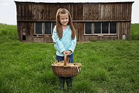 Girl 5_6 holding egg basket at farm portrait