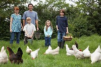 Parents with three children 5-9 feeding hens in garden portrait (thumbnail)
