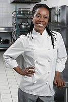 Female chef with hand on hip in kitchen portrait