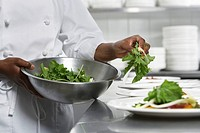 Chef preparing salad in kitchen mid section (thumbnail)