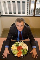 Businessman with tray of vegetables