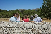 Three_generation family with two children 6_11 by stone wall back view