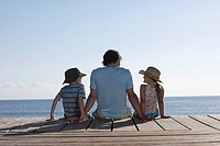 Father and two children 7-9 sitting on jetty back view (thumbnail)