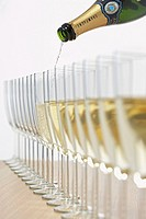 Bottle of champagne filling row of glasses selective focus