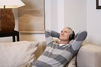 Middle_aged man listentening to music on headphones in living room