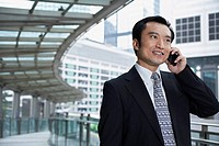 China Hong Kong business man using mobile phone standing on footbridge