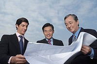 Three business holding and looking at blueprints smiling