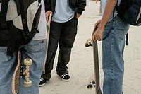 Cropped view of three teenage boys holding skateboards.