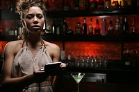 Young woman at a bar with a cell phone