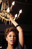 Young ethnic woman touching a chandelier
