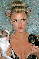 Woman wearing curlers holding two dogs