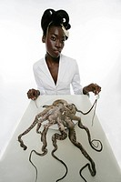 Woman sitting at a table with a raw octopus