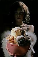 Woman looking at camera, holding a bowl of cinnamon buns
