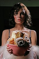 Woman looking at camera, holding a bowl of cinnamon buns