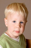 A blonde-hair, blue-eyed two year old boy looks straight at the camera. He is wearing a white t-shirt and green jumper