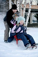Mother and children sledging down a hill.