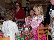 Children with Crackers at the Christmas Dinner Table Child Opening a Present from the Cracker