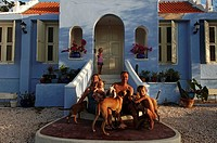 Netherlands Antilles, Curacao, expat family posing on the steps of their historical colonial Dutch cottage