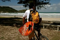 Surfer with bicycle and surfboard, Bombas, Santa Catarina, Brazil