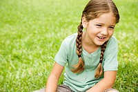 little girl with pigtails sitting on the grass