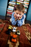 little boy playing with toy cars on the floor