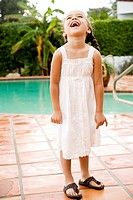little Hispanic girl laughing standing by pool