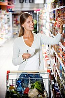 Woman reaching up to get something off of a supermarket shelf