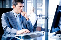 Businessman sat at a desk using a computer looking stressed