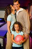 Family in a bowling alley, daughter holding a red bowling ball