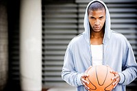 Portrait of a young African American man in a grey hooded top holding a basketball